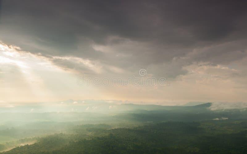 阳光通过云彩发光入山和森林 免版税库存图片