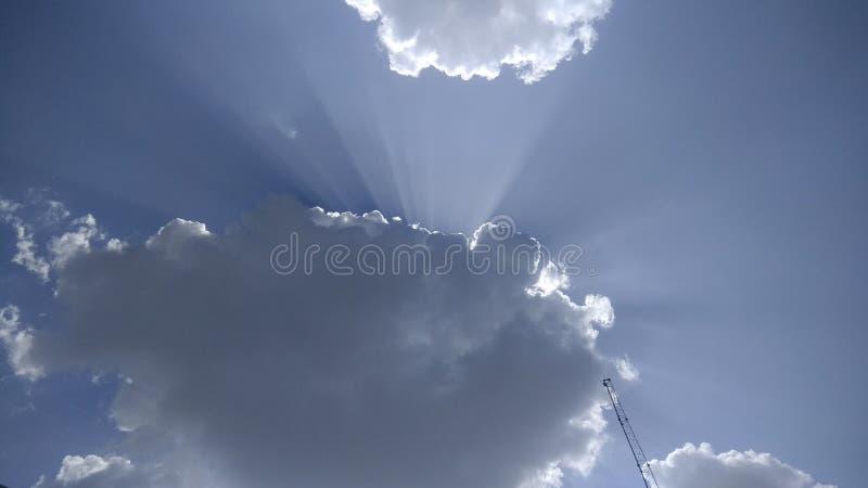 阳光通过在天空蔚蓝的白色云彩 库存照片