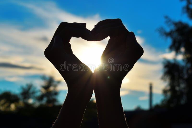 阳光通过棕榈 女性手黑暗的剪影在日落的在天空 免版税库存图片