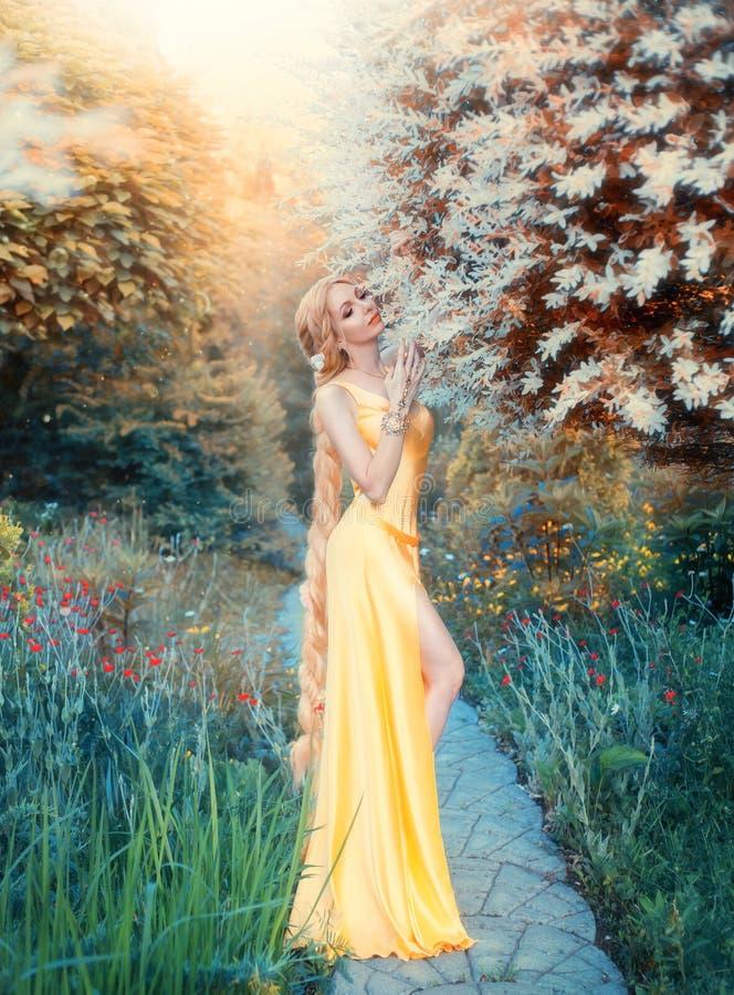 阳光,壮观的柔和的诱人的黄色礼服的亭亭玉立的女孩新生世纪,夫人的人类化与 库存图片