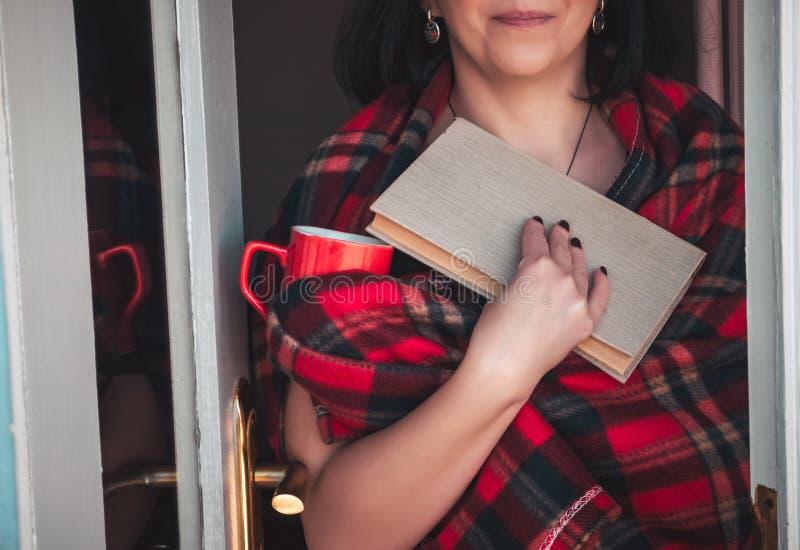 阳台的妇女有书的 免版税库存照片