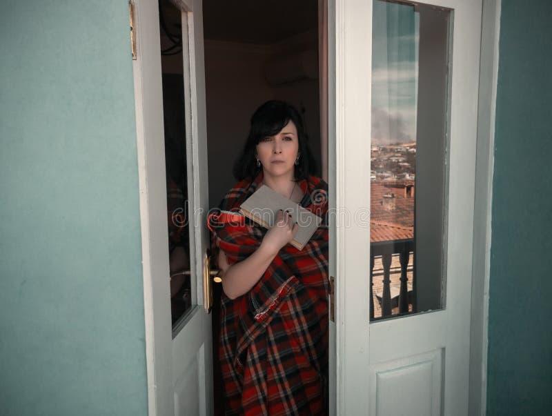 阳台的妇女有书的 免版税图库摄影