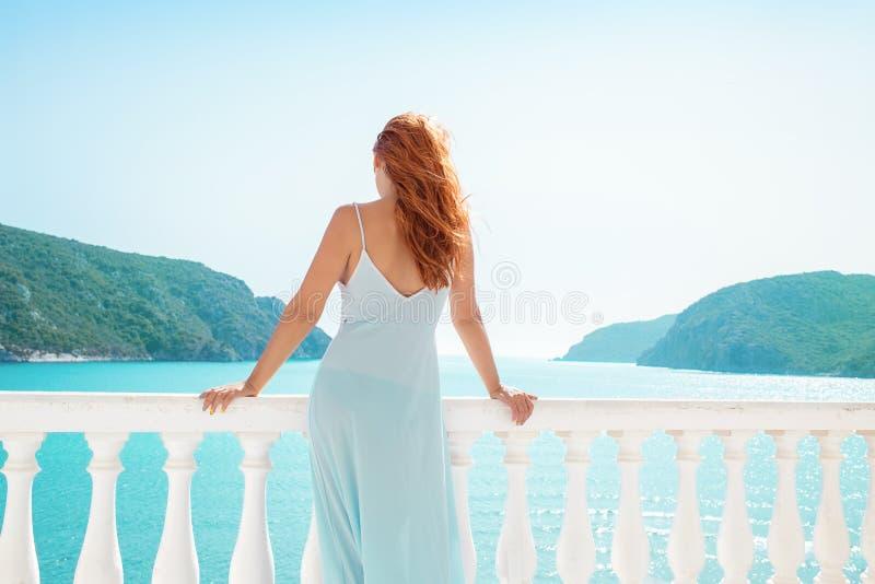 阳台的妇女有热带海景的 库存照片