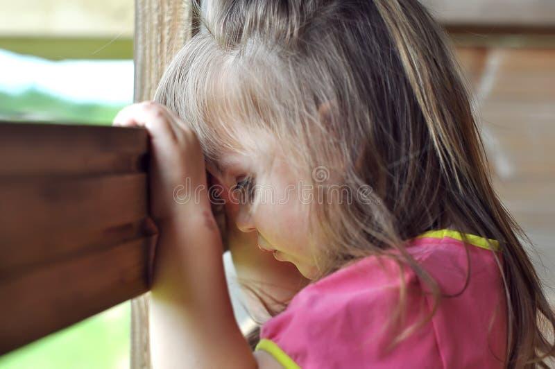 阳台的,从窗口的神色相当微笑的小女孩 库存图片