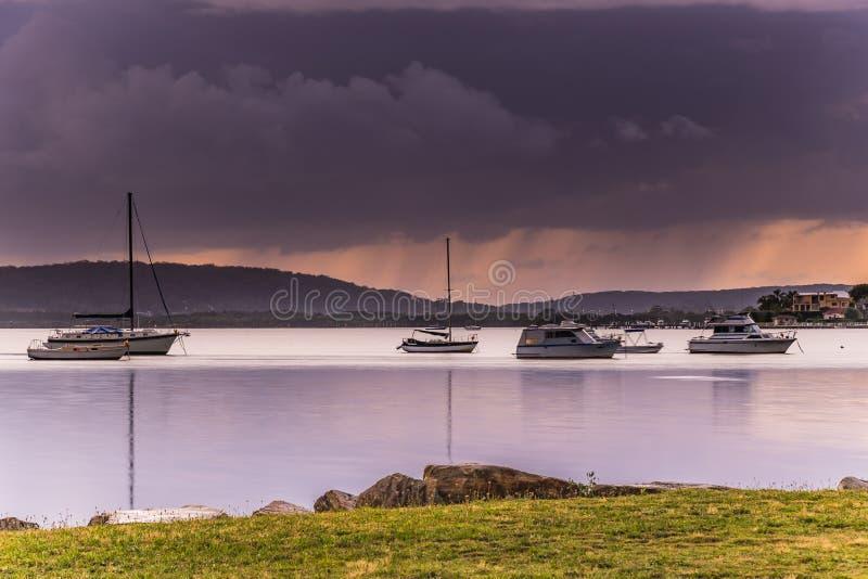阴云密布和雨横跨海湾与小船 库存图片