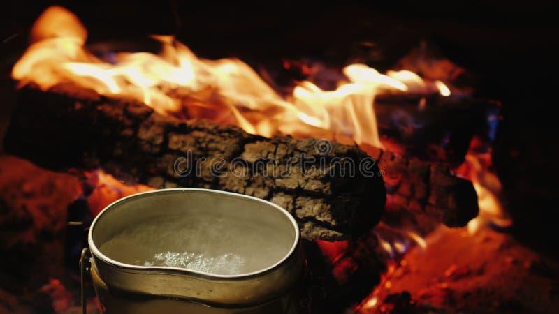 阵营水壶在火附近煮沸 热的茶和食物的准备在远足 免版税库存图片