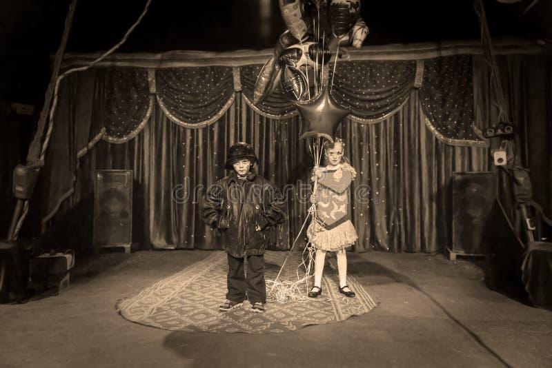 阶段的男孩小丑与拿着气球的女孩 免版税库存照片