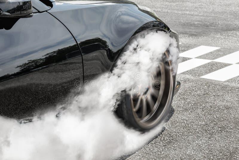 阻力赛车烧轮胎在起动线 免版税库存图片