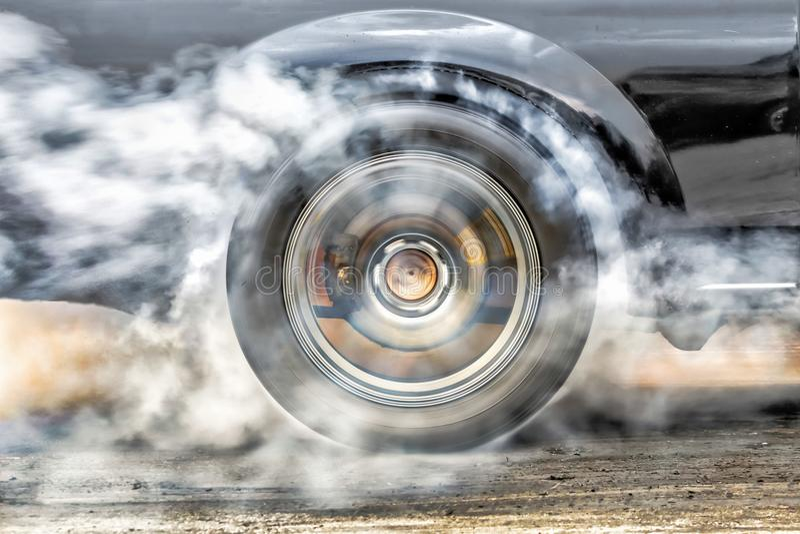 阻力赛车烧轮胎在起动线 库存照片