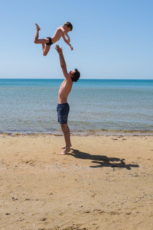 阻止在他的年轻愉快的父亲武装举起他的小儿子在海滩 免版税图库摄影