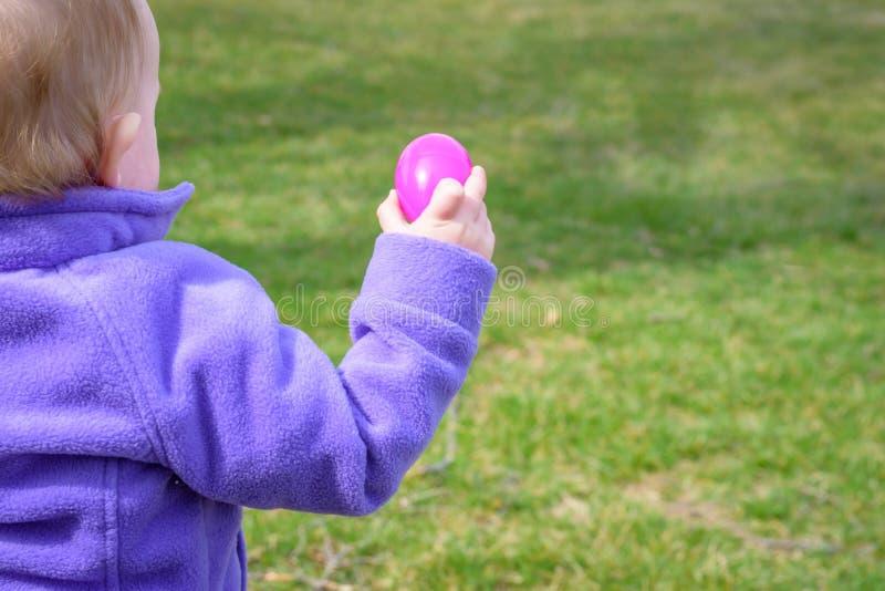 阻止塑料复活节彩蛋的小女孩外面 图库摄影