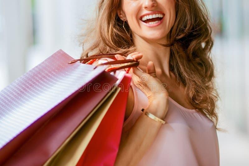 阻止购物带来的棕色毛发,愉快,微笑的妇女 图库摄影