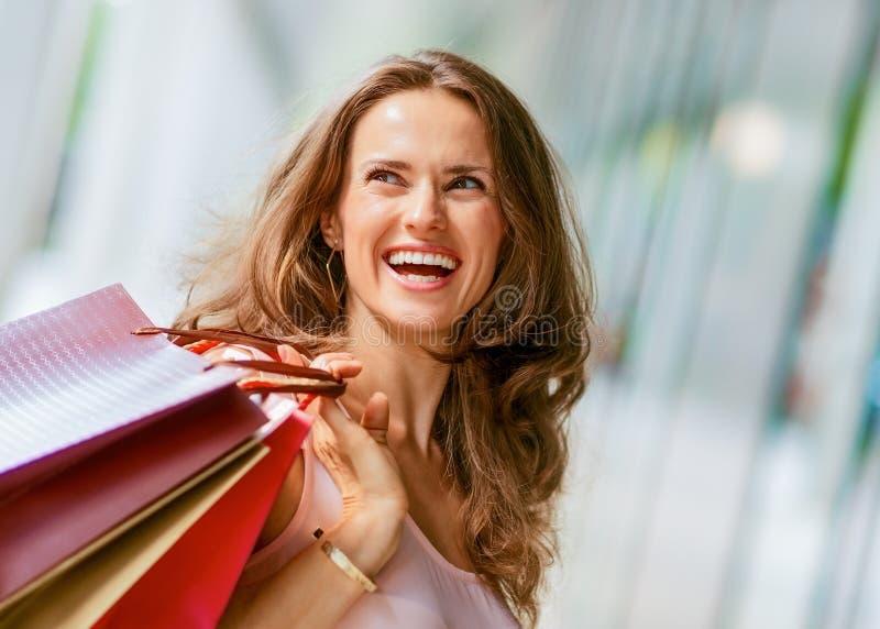 阻止购物袋的棕色毛发,愉快,微笑的妇女 图库摄影