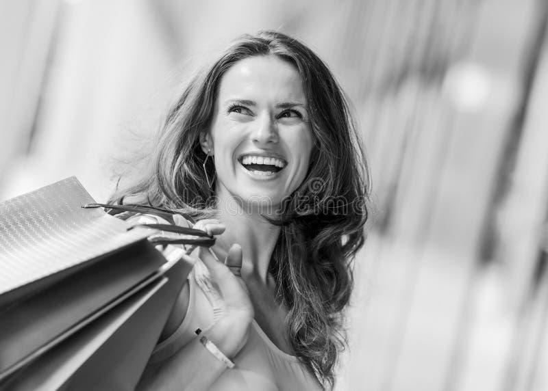 阻止购物袋的棕色毛发,愉快,微笑的妇女 免版税图库摄影