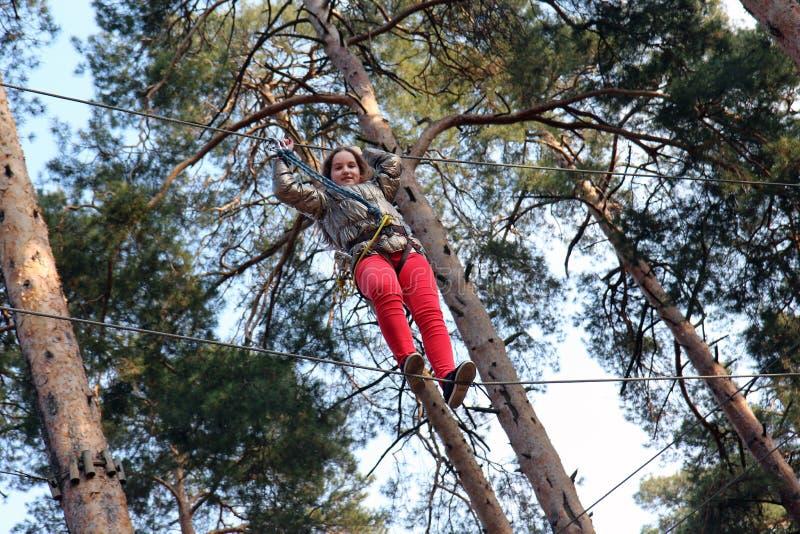 阻碍解决 上升在一条绳索的女孩在冒险公园 图库摄影