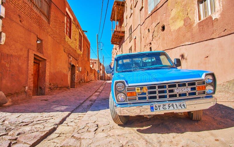阿卜亚内赫,伊朗- 2017年10月23日:葡萄酒蓝色汽车在历史的山村中世纪街道停放,10月23日  库存照片