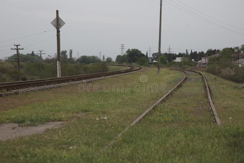阿塞拜疆铁路与在绿色背景的天空 铁路通过春天绿色领域挺直转动 在那里距离 库存照片