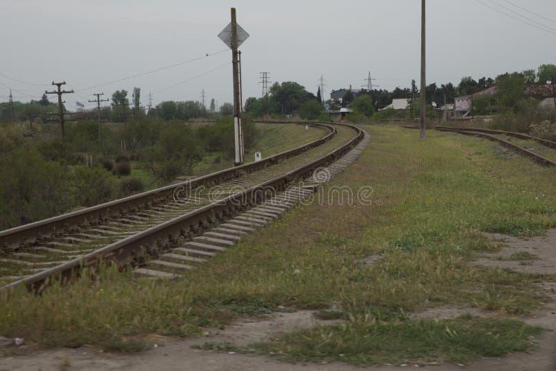 阿塞拜疆铁路与在绿色背景的天空 铁路通过春天绿色领域挺直转动 在那里距离 免版税图库摄影