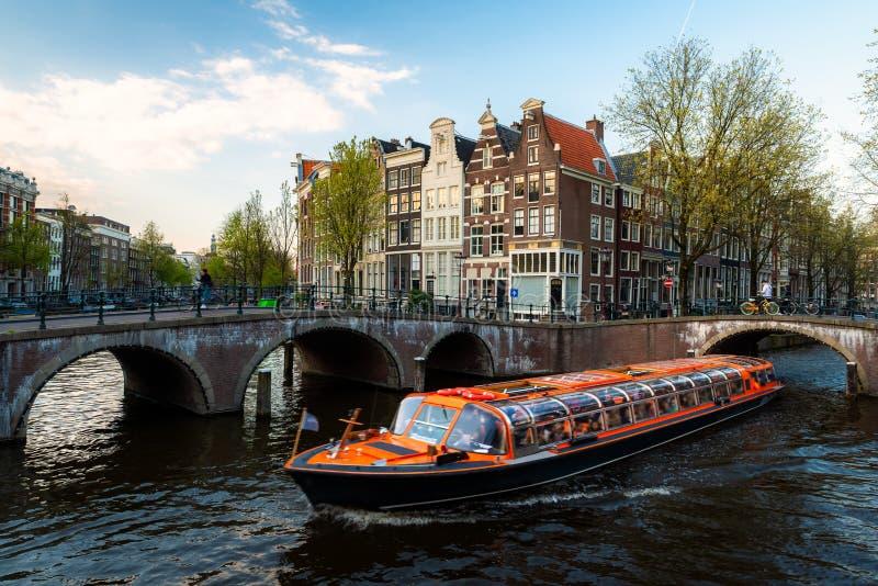 阿姆斯特丹运河与荷兰传统房子的游轮在阿姆斯特丹,荷兰 免版税图库摄影