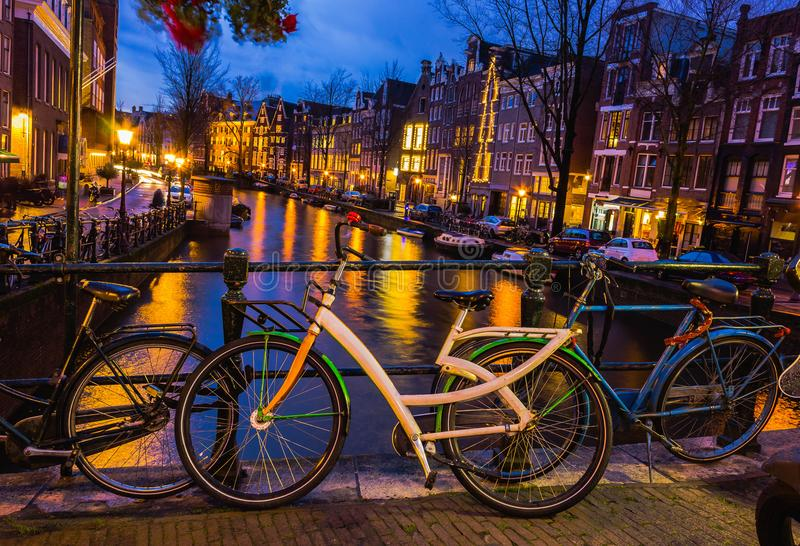 阿姆斯特丹运河和桥梁的夜照明有典型的荷兰房子、小船和自行车的 库存照片