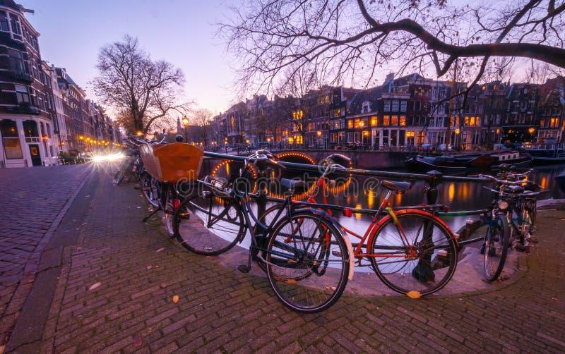 阿姆斯特丹运河视图和自行车在桥梁在晚上 免版税库存照片