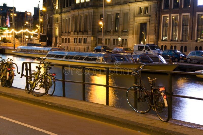 阿姆斯特丹骑自行车小船运河荷兰晚上 免版税图库摄影