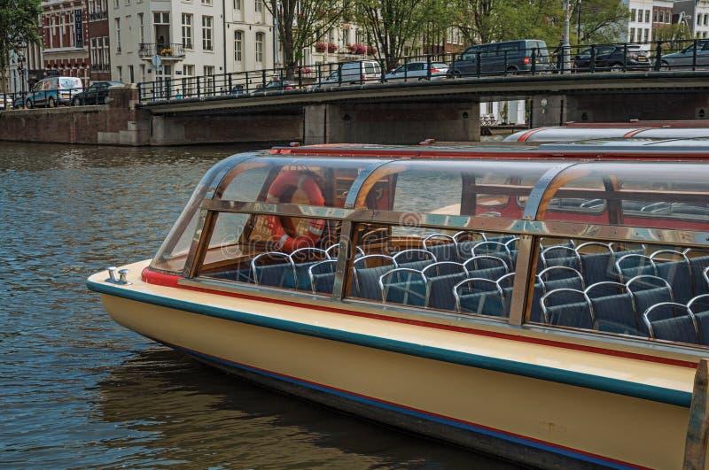 阿姆斯特丹,北荷兰- 2017年6月27日 旅游小船和桥梁在宽运河在晴天在阿姆斯特丹 免版税库存图片