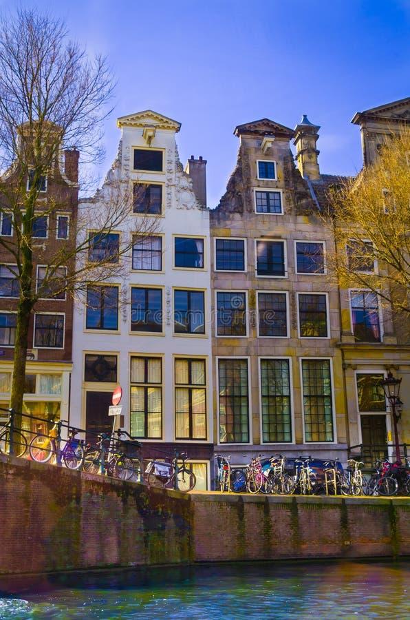 阿姆斯特丹,荷兰, 2018年4月, 23 :有些自行车室外看法在运河的河沿连续停放了  免版税图库摄影