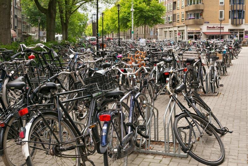 阿姆斯特丹,荷兰- 2017年6月25日:停放与在其中一条的许多自行车中央街道 库存照片