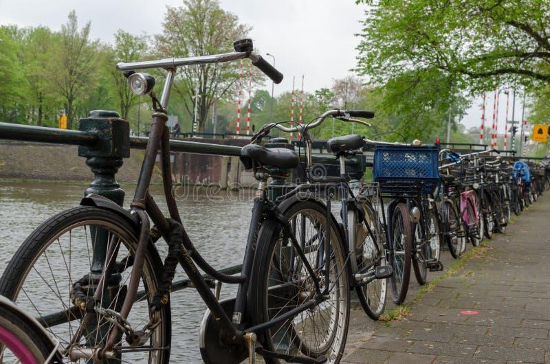 阿姆斯特丹,荷兰- 2019年5月03日:在线的很多自行车由河运河 低点视图 免版税库存图片
