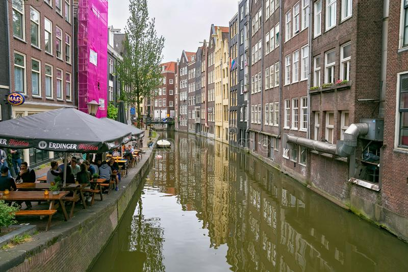 阿姆斯特丹,荷兰- 2017年6月25日:在那个的老大厦在历史部分的水运河附近 免版税库存图片