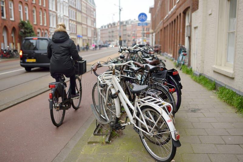 阿姆斯特丹,荷兰- 2019年3月21日:妇女在阿姆斯特丹的中心骑一辆自行车 欧洲的自行车首都 免版税库存照片