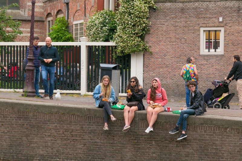 阿姆斯特丹,荷兰- 2017年6月25日:小组未知的年轻女人吃在运河银行的便当 免版税库存图片