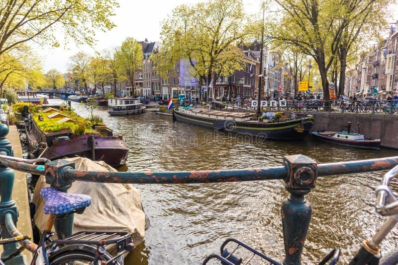 阿姆斯特丹,荷兰- 2019年4月13日:排行在阿姆斯特丹运河的自行车一座桥梁  库存照片