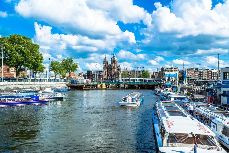 阿姆斯特丹,荷兰- 2015年5月28日:运河的堤防在有游船的阿姆斯特丹在一个晴天 库存照片