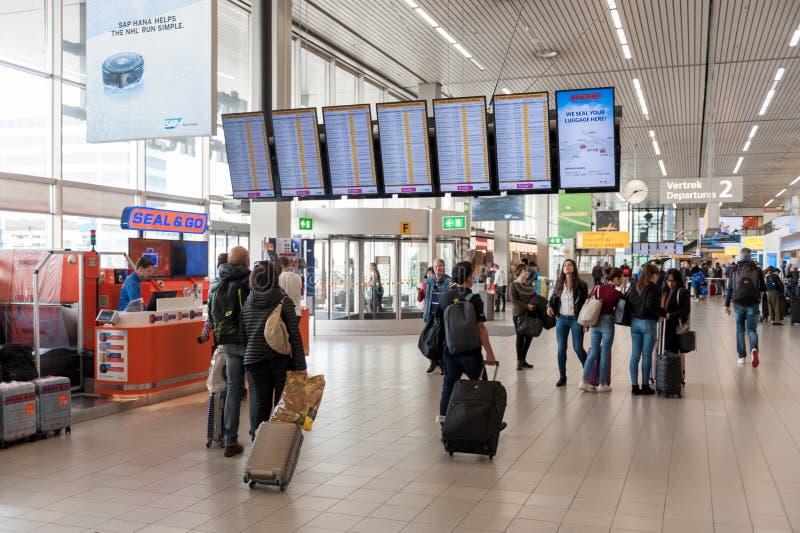 阿姆斯特丹, NETHERLAND - 2017年10月18日:与乘客的国际阿姆斯特丹史基浦机场内部 屏幕和人们 库存图片