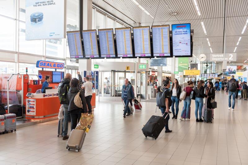 阿姆斯特丹, NETHERLAND - 2017年10月18日:与乘客的国际阿姆斯特丹史基浦机场内部 屏幕和人们 免版税图库摄影