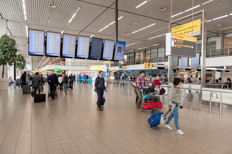 阿姆斯特丹, NETHERLAND - 2017年10月18日:与乘客的国际阿姆斯特丹史基浦机场内部 屏幕在背景中 库存照片