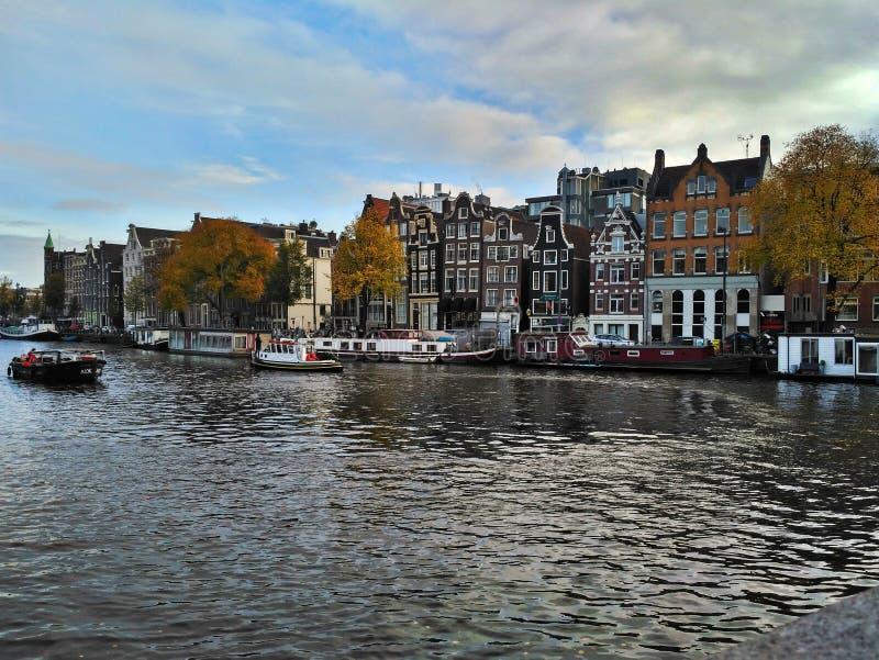 阿姆斯特丹/荷兰- 2016年10月30日:在阿姆斯特丹运河、小船和传统荷兰房子的看法 免版税库存图片