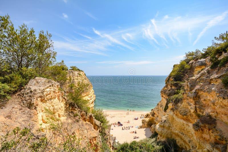 阿尔加威葡萄牙:在峭壁的巨大的岩石使普腊亚da Marinha,在Lagoa附近的可爱的暗藏的海滩靠岸 库存照片
