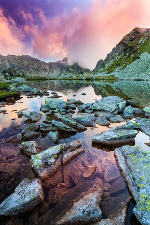 阿尔卑斯和暴风云的原始冰川湖在日落 库存图片