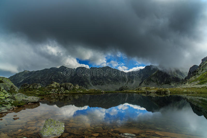 阿尔卑斯和暴风云的原始冰川湖在日落 图库摄影