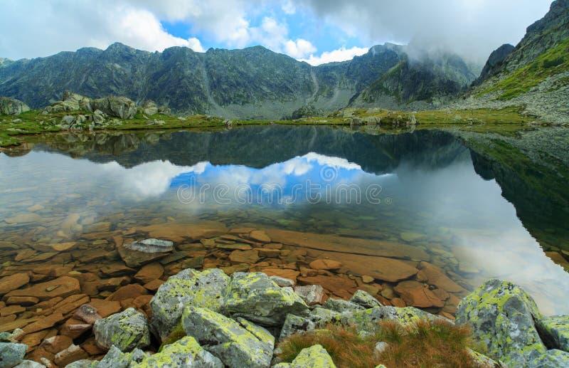 阿尔卑斯和暴风云的原始冰川湖在日落 免版税库存照片