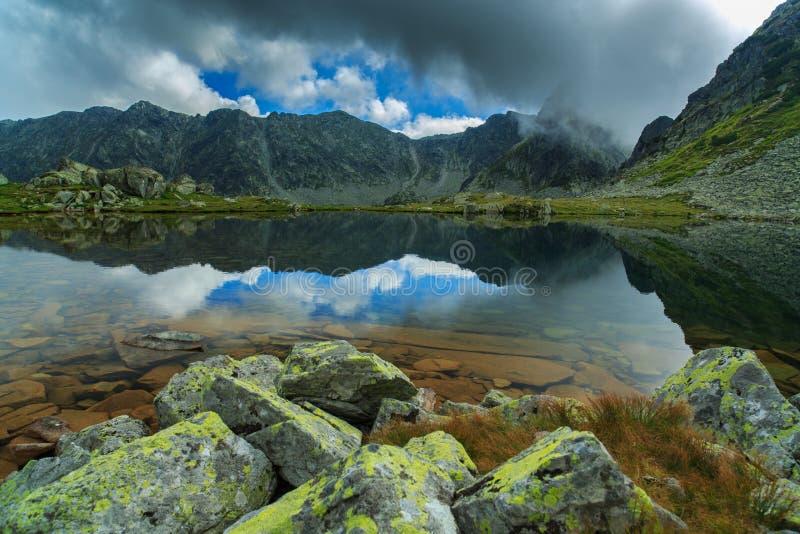 阿尔卑斯和暴风云的原始冰川湖在日落 免版税库存图片