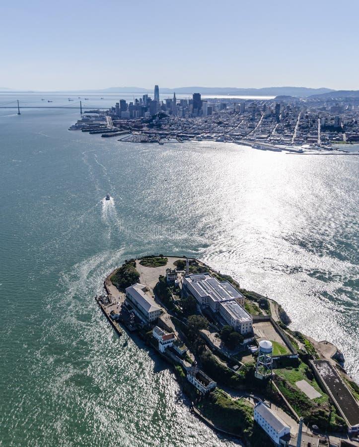 阿尔卡特拉斯岛监狱的航空摄影在前景的与旧金山和海湾桥梁 免版税库存图片