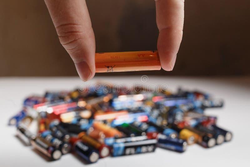 阿尔汉格尔斯克,俄罗斯,2018年12月3日:回收的概念 使用的被弄脏的碱性电池在手中和很多使用 免版税库存照片