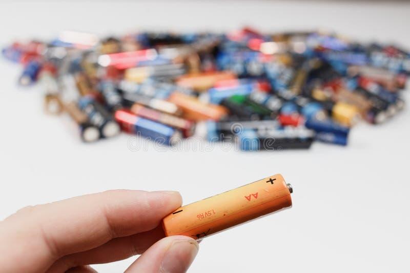 阿尔汉格尔斯克,俄罗斯,2018年12月3日:回收的概念 碱性电池在手中和很多被弄脏的碱性 免版税库存图片