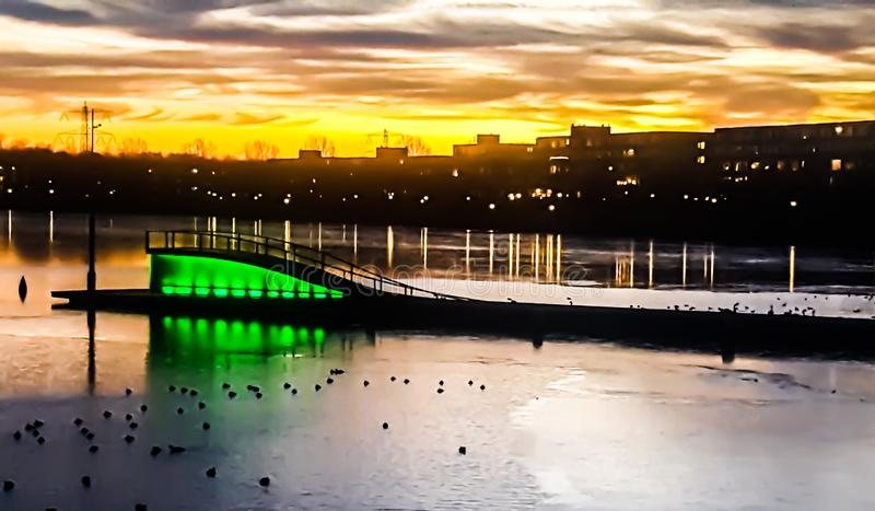 阿尔米尔斯塔德的夕阳 湖桥屋的绿色也可见 阿尔米尔 大能形 免版税库存照片