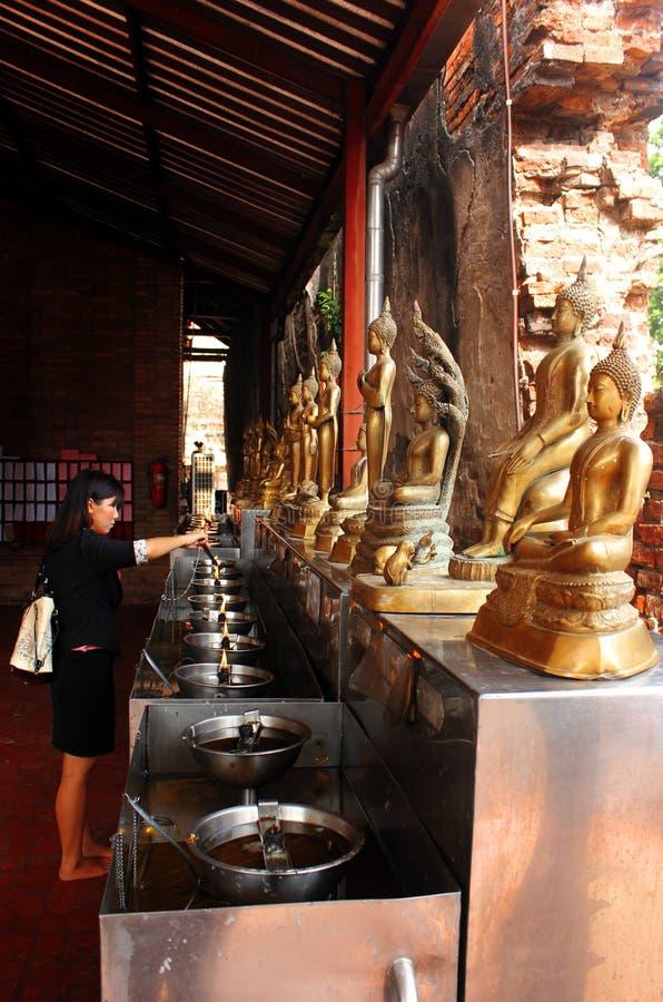 阿尤特拉利夫雷斯,泰国- 2014年4月29日 佛教寺庙的妇女点燃一个打火机作为提供 免版税图库摄影