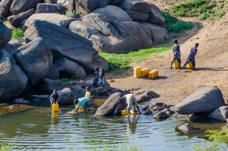 阿布贾,尼日利亚- 2014年3月13日:填装黄色水容器的未认出的幼儿在河 库存图片